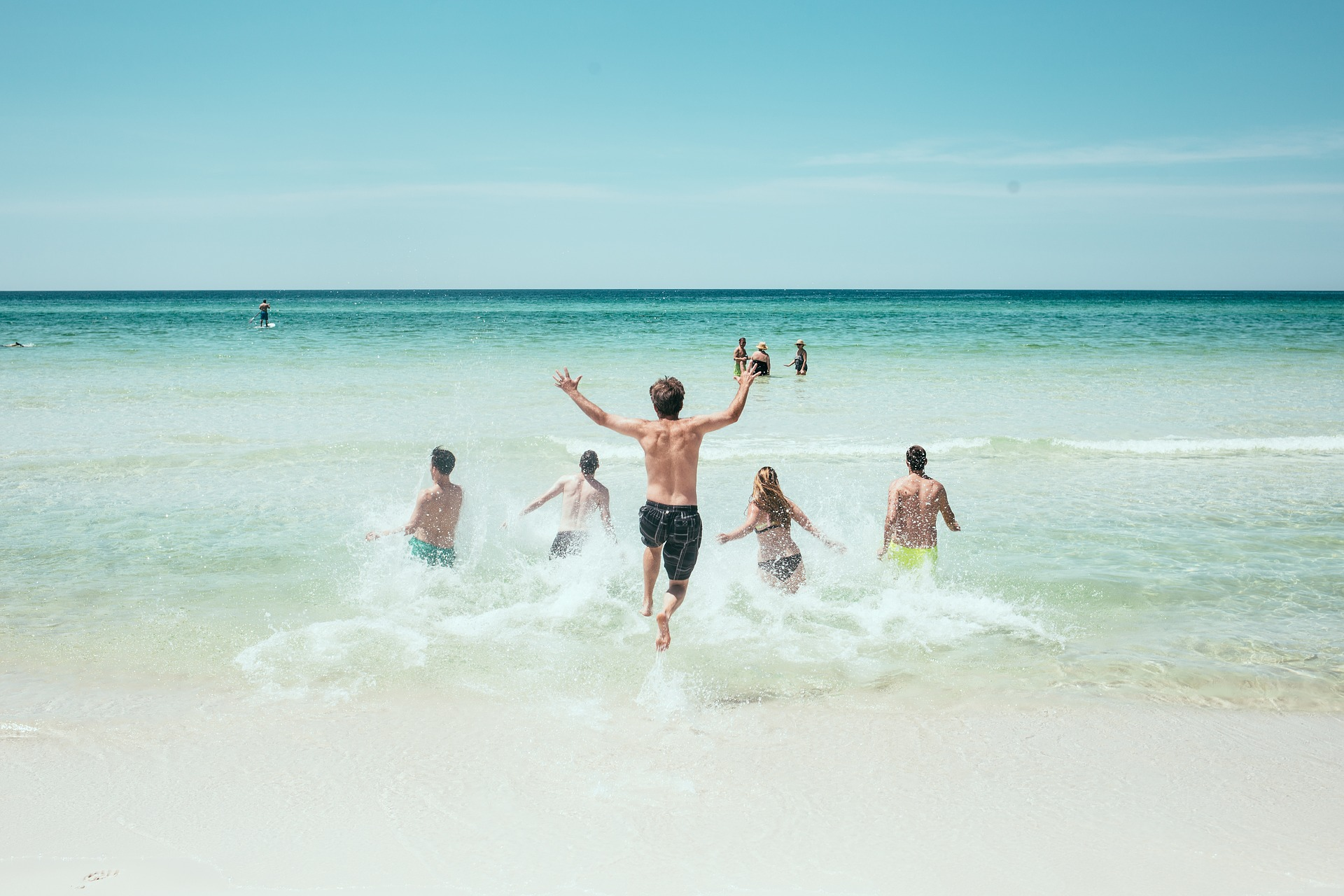 group of friends running into the ocean on a sunny day